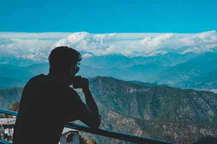 man in black shirt standing on top of mountain drinking coffee