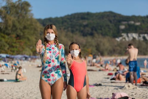 A woman and a child in a protective surgical mask on their face are standing on the beach in swimsuits. Chinese coronavirus disease COVID-19 is dangerous